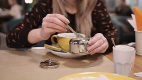 Uma mulher unidentifiable derrama o açúcar com uma colher em um copo em um restaurante Movimento lento vídeos de arquivo