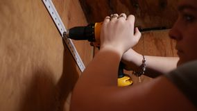 Uma mulher usa a broca elétrica da chave de fenda para ancorar um feixe de apoio filme