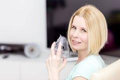 Uma mulher usa um inalador Foto de Stock Royalty Free