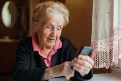Uma mulher usa um phon esperto imagens de stock royalty free