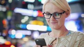 Uma mulher usa um smarf em uma cidade grande contra um fundo de luzes de anúncio borradas Popular entre o tempo dos turistas filme