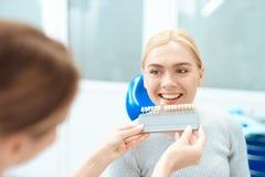 Uma mulher veio ver um dentista para clarear dos dentes O dentista determina a cor de seus dentes Imagem de Stock