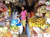 Uma mulher vende uma grande variedade de bens frescos, crus e secos em uma loja comercial Imagens de Stock Royalty Free