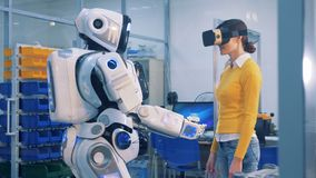 Uma mulher verifica um droid, vestindo vidros de VR Conceito da realidade virtual vídeos de arquivo