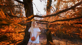 Uma mulher vestiu em um vestido branco com posses do bordado uma abóbora Fotografia de Stock
