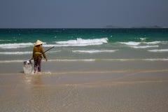 Uma mulher vietnamiana está recolhendo shell do mar na costa em Nha Trang, Vietname Fotos de Stock Royalty Free