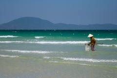 Uma mulher vietnamiana está recolhendo shell do mar na costa em Nha Trang, Vietname Imagem de Stock
