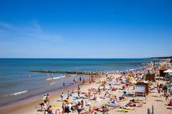 Uma multidão de banhistas na praia situada na costa de mar Báltico, Rússia de Zelenogradsk fotografia de stock royalty free
