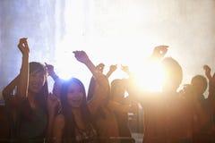 Uma multidão de jovens que dançam em um clube noturno Fotografia de Stock Royalty Free