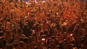 Uma multidão de povos em um concerto de rocha Os fãs recolhem na frente do desempenho de um grupo de rock video estoque
