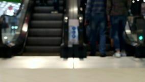 Uma multidão de povos levanta-se e monta-se em uma escada rolante no aeroporto, borrado, fundo filme