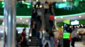 Uma multidão de povos levanta-se e monta-se em uma escada rolante no aeroporto, borrado, fundo video estoque