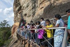 Uma multidão de povos que movem-se para o frescoe cava na rocha de Sigiriya em Sri Lanka central Fotografia de Stock Royalty Free