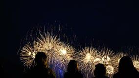 Uma multidão de povos que olham uma saudação brilhante grande no céu noturno, filmada em smartphones video estoque