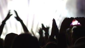Uma multidão feliz que tem uma grande estadia em uma mostra do concerto filme