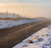 Uma névoa profunda aumenta de uma estrada secundária no meio do inverno, 2019 fotos de stock