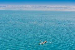 Uma natação da mulher que banha o Mar Morto Jordânia foto de stock