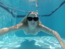 Uma natação da mulher sob a água Imagens de Stock