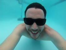 Uma natação do homem sob a água Imagem de Stock