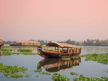 Uma navigação da casa flutuante em marés de kerala durante o por do sol imagem de stock royalty free