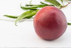 Uma nectarina na tabela Imagens de Stock Royalty Free
