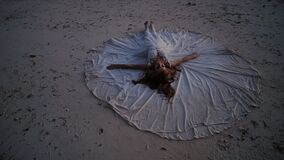 Uma noiva bonita e feliz encontra-se na areia durante o por do sol, espalhando um vestido de casamento em torno dela A ideia orig filme
