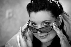 Uma noiva bonita nos vidros e em um véu branco olha com um brilho fotos de stock