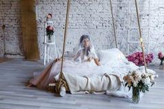 Uma noiva com penteado e compõe no vestido de casamento cor-de-rosa lindo e em um vail com um ramalhete das peônias Foto de Stock