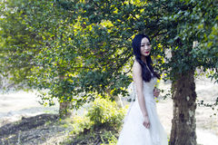 Uma noiva com suporte branco do vestido de casamento no meio das árvores Fotografia de Stock Royalty Free