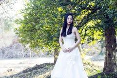 Uma noiva com suporte branco do vestido de casamento no meio das árvores Imagem de Stock Royalty Free