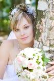 Uma noiva com um ramalhete da flor pela árvore Fotos de Stock