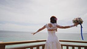 Uma noiva de brilho aprecia a felicidade da altura do balcão que negligencia o oceano e os recifes Voo do amor exotic filme