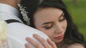Uma noiva dos jovens abraça seu amante e fecha seus olhos com prazer Pares loving que abraçam-se no por do sol amar video estoque