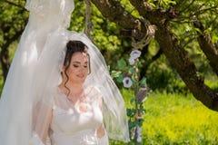 Uma noiva fantástica no parque senta-se no balanço e olha-se o vestido de casamento Fotografia de Stock