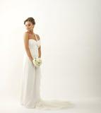 Uma noiva triguenha nova em um vestido branco com rosas Imagens de Stock Royalty Free