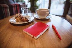 Uma nota vermelha e uma pena vermelha estão na tabela em um café, em uma xícara de café e em um croissant no fundo fotografia de stock