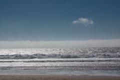 Uma nuvem e ondas que alcançam a costa imagem de stock