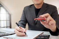 Uma oferta do corretor de seguro do homem protege seu carro imagem de stock