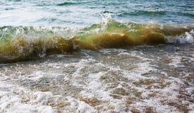 Uma onda da cor verde delicada com areia amarela para dentro foto de stock royalty free