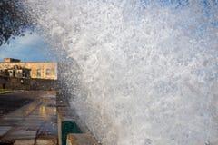 Uma onda de oceano deixa de funcionar sobre uma paredão a um fotógrafo e ao fim da terraplenagem da frente marítima acima Ilha de foto de stock royalty free