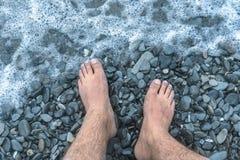 Uma onda em uma praia de pedra coberta com as rochas, pés masculinos do mar na onda de espirro foto de stock