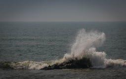 Uma onda que espirra contra uma rocha contínua no oceano Foto de Stock Royalty Free