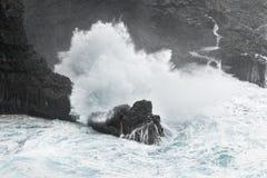 Uma onda quebra no clima de tempestade em uma costa rochosa imagem de stock