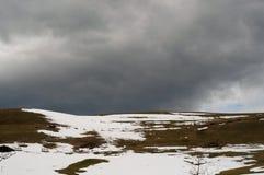 Uma opinião do campo de um monte com a grama verde coberta com a neve ao princípio de abril fotos de stock royalty free