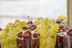 Uma opinião do close-up da água deixa cair a queda em cerejas vermelhas frescas da variedade e em uvas verdes em uns copos no mer Fotografia de Stock Royalty Free