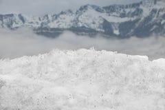Uma opinião do close-up de uma pilha da neve em um fundo da montanha imagens de stock royalty free