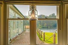 Uma opinião do lago através de um quadro de janela com uma ampola foto de stock