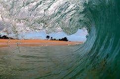 Uma opinião dos surfistas de uma onda imagens de stock