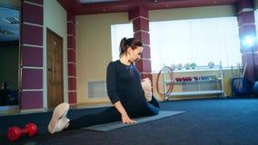 Uma opinião impressionante uma jovem mulher no leggins pretos que faz uma separação lateral e o esticão para fora em um gym vídeos de arquivo
