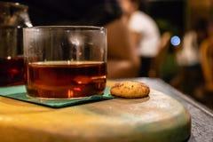Uma opinião lateral do close up de um vidro do chá e da cookie fotografia de stock royalty free